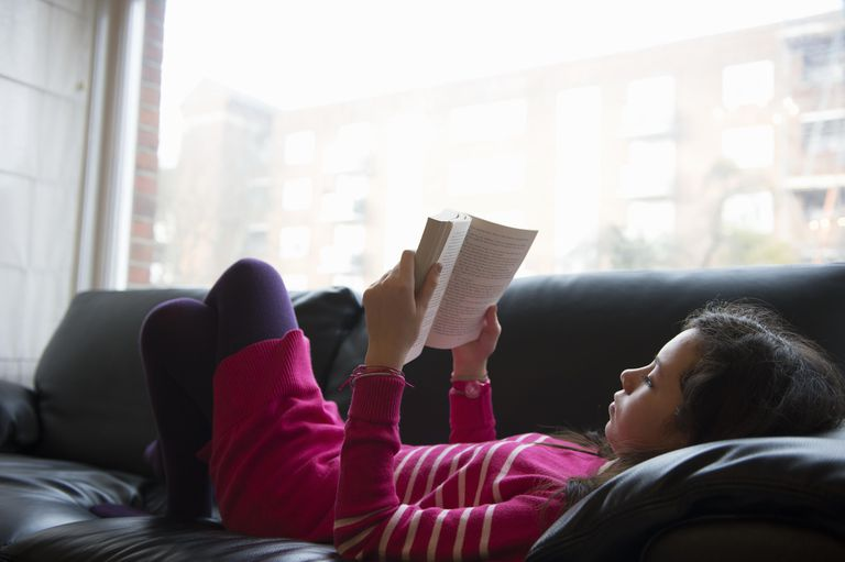Girl lying on sofa, reading book