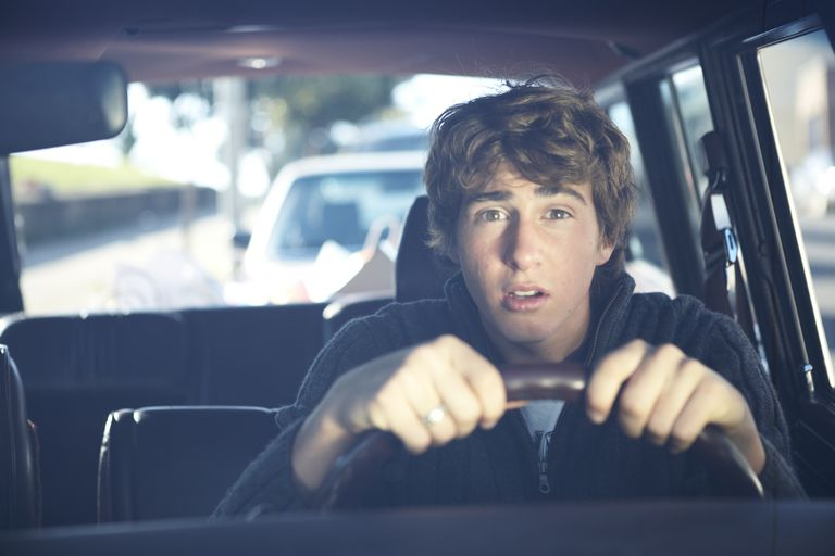 Teenage boy driving car