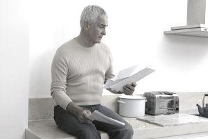 Mature man sitting on kitchen worktop, reading bills