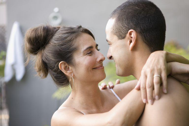Couple hugging in backyard garden