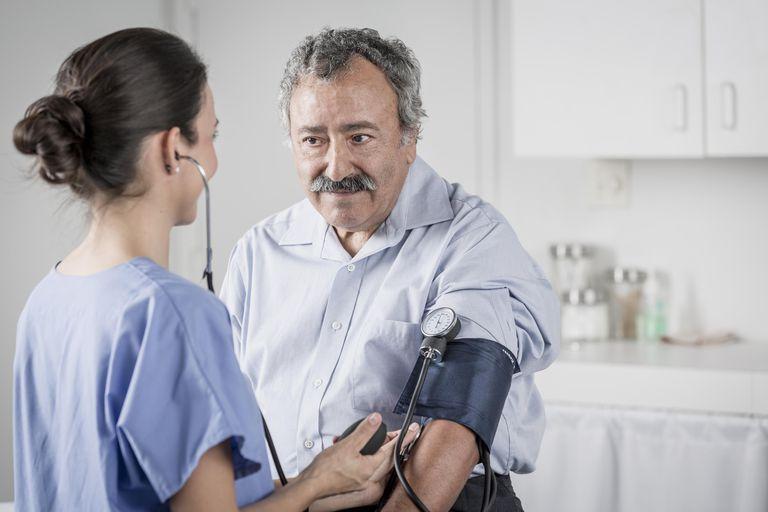 Nurse checking senior man's blood pressure