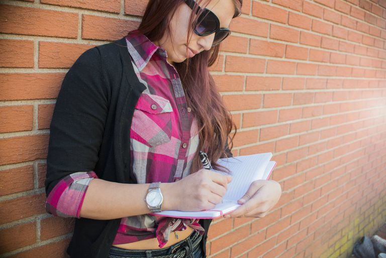 Young woman leaning against brick wall writing in notebook