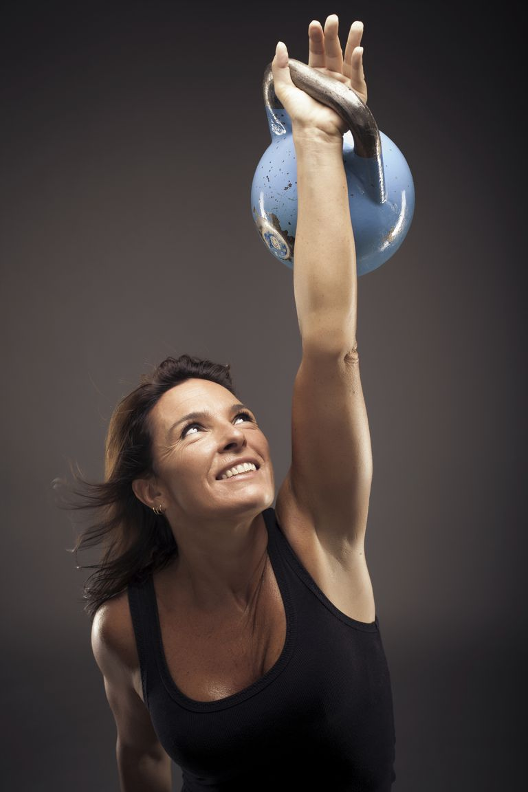 Woman pressing a Kettlebell