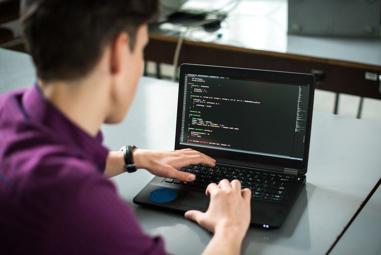 Young man coding on his computer