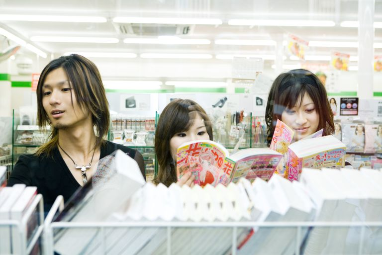Three young friends side by side in store, looking at manga-style comic books
