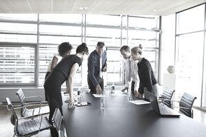 Business people looking at paper in meeting room