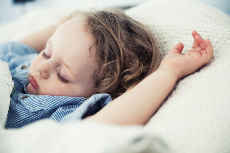 Sleeping male toddler with arms up on pillow