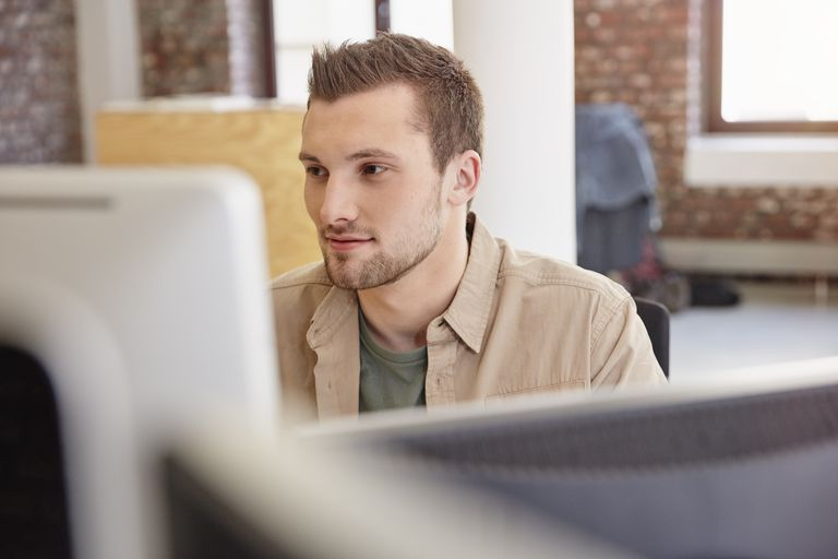 Young man sitting in office using computer