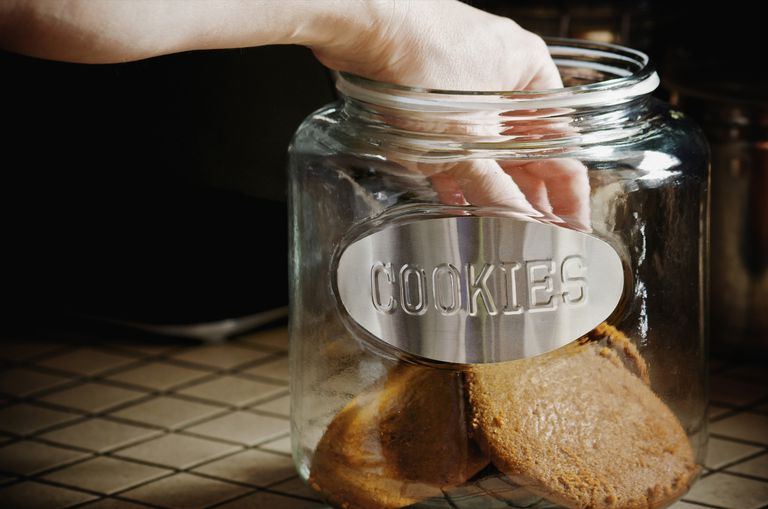 Adult hand in a glass cookie jar
