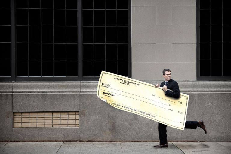 Man running down sidewalk with a giant check, similar to the ones PCH awards.