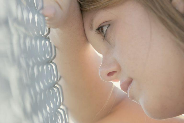 Sad young teen staring at fence
