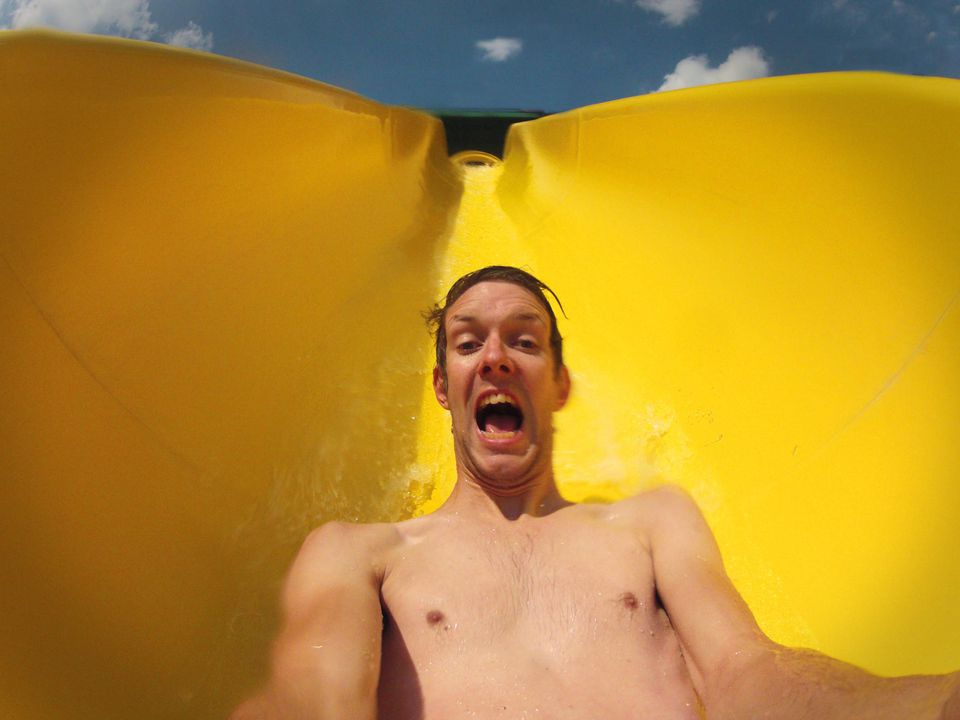 A man riding a yellow waterslide