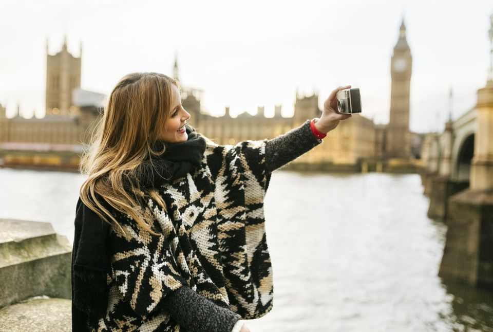 UK, London, young woman taking a selfie near Westminster Bridge