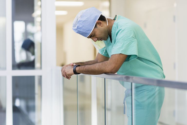 Surgeon leaning on handrail in corridor