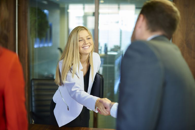 young woman shaking hands in job interview