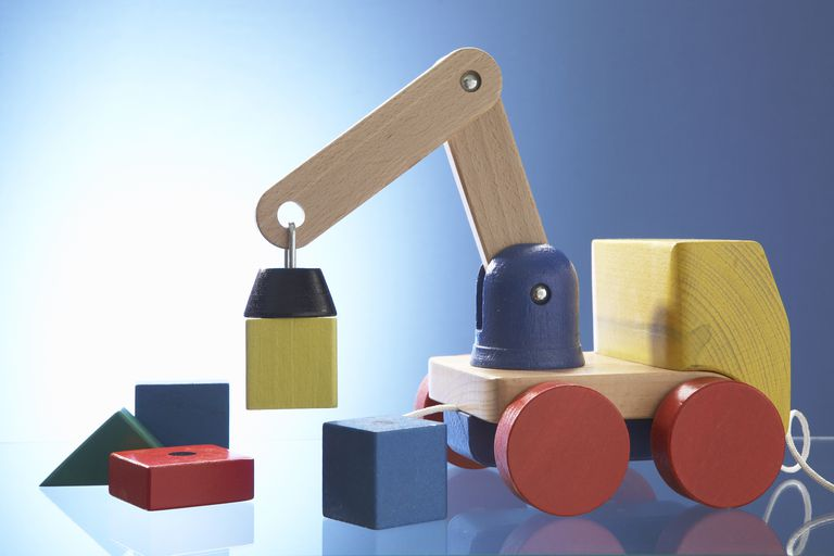 The yellow block held by the toy's magnet exerts a downward force due to gravity and an opposing upward force.