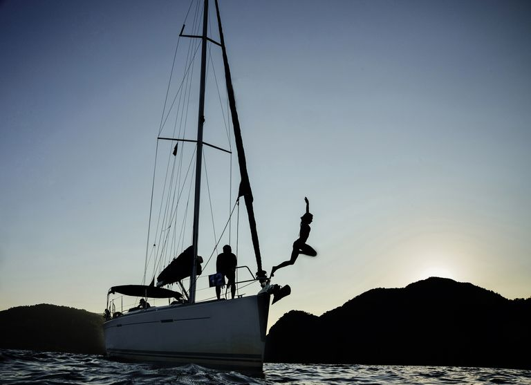 Silhouette of girl jumping off sailboat