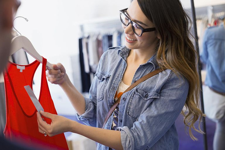 Woman checking price on tank-top in shop