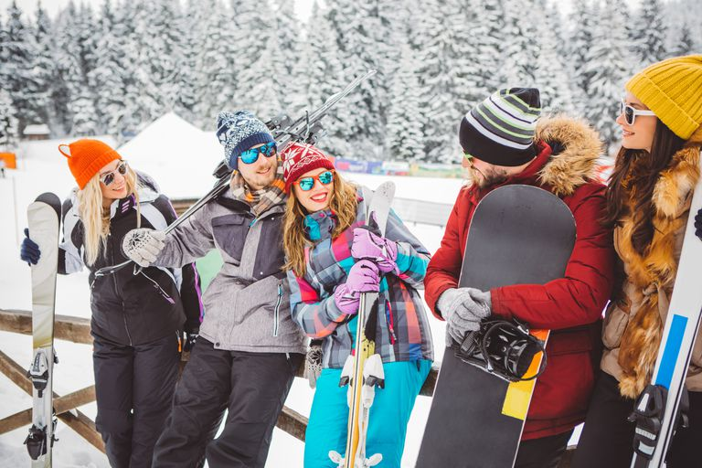 Friends on vinter vacation at mountain. Relaxing on a patio, at a ski resort. Preparing for skiing.