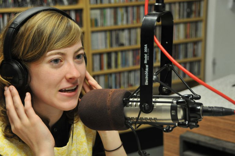A woman speaking into a radio broadcasting microphone while wearing headphones