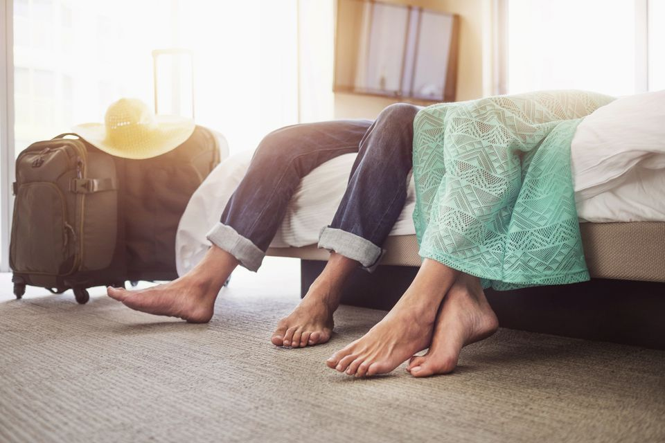 Legs of couple laying on bed in hotel room