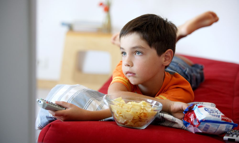 junk food ads - boy watching TV with chips and cookies