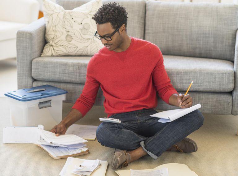 Man sitting on floor calculating bills
