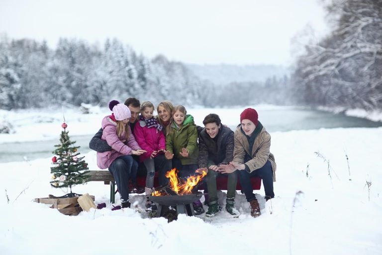 Family sitting at campfire in snow