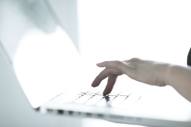 hand typing on laptop keyboard