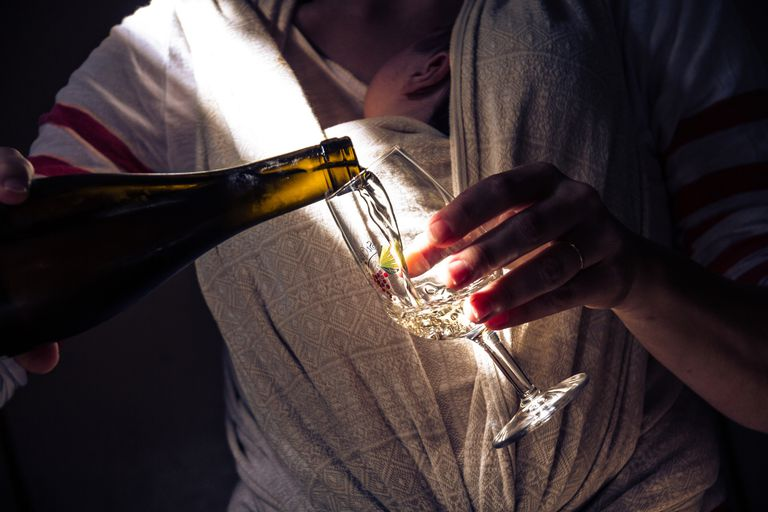 Close-Up Of Woman Pouring Wine From Bottle