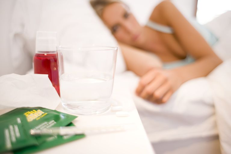 cold medicine on nightstand with woman in bed in background