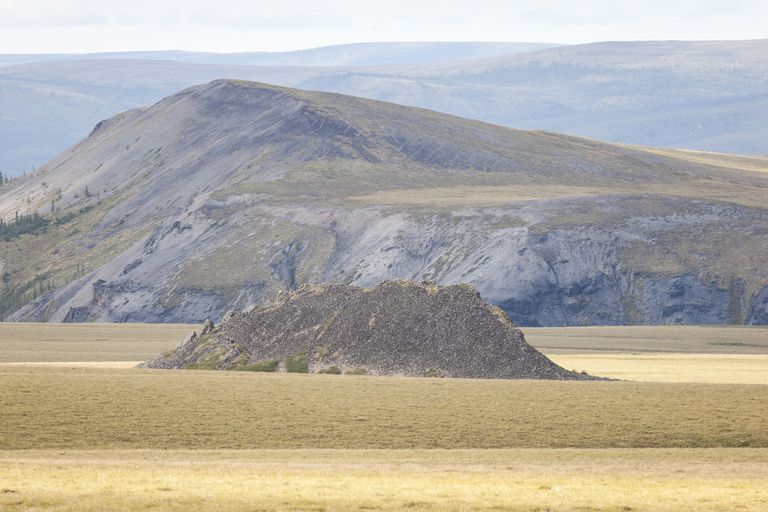Permafrost landscape with a pingo hilltop in the mid-ground and mountains in the distance. Yukon Territories, Canada.