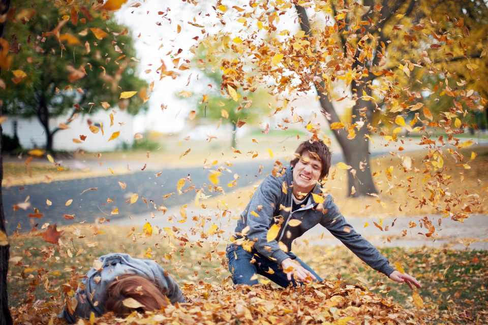 Two kids playing in a pile of fallen leaves.