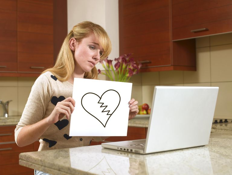 Woman on the internet with a broken heart sign