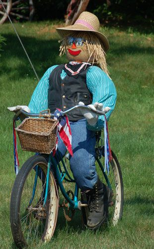 Picture: scarecrow with hat on bike. Scarecrow in photo wears glasses.