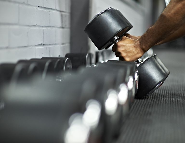 Athletic Male Picking Up Dumbbells in Gym