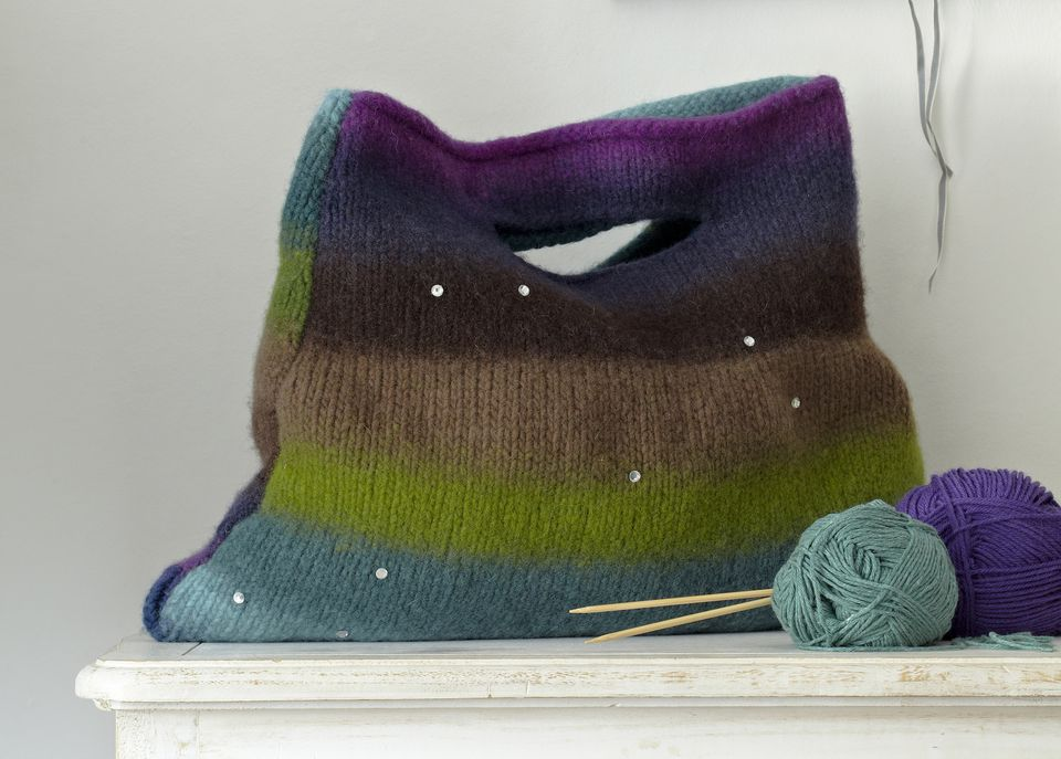 Stripy felted tote bag on chest of drawers and balls of wool