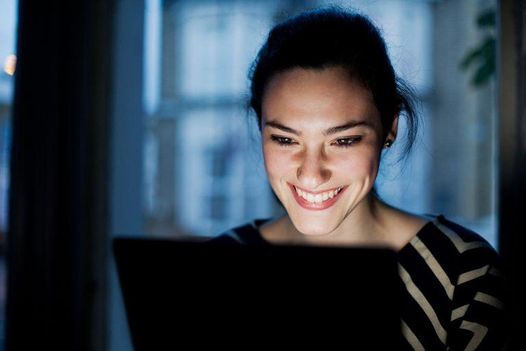 Woman lit by screen.