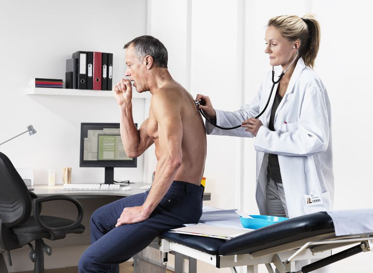 Man coughing at visit with a doctor.