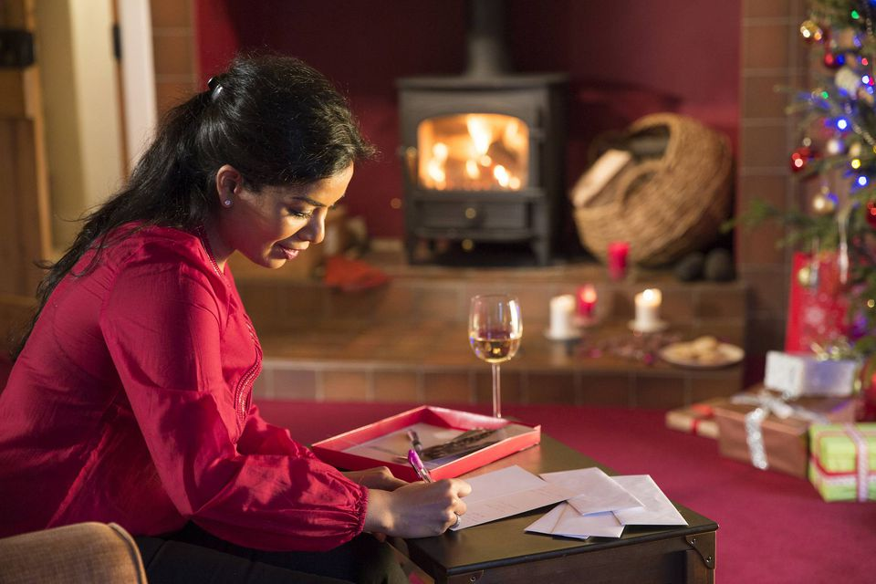 A picture of a woman writing Christmas cards