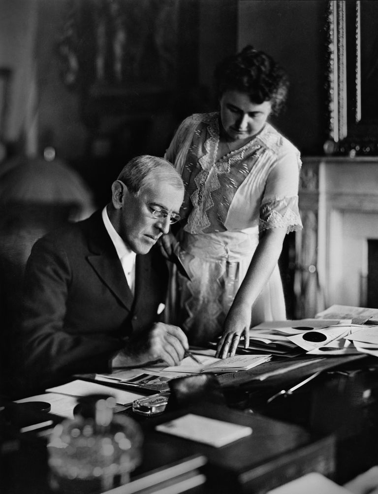 President Woodrow Wilson and his wife Edith review papers in the Oval Office