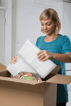 a woman packing a box