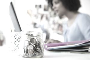 Woman working on computer with jar of money in foreground