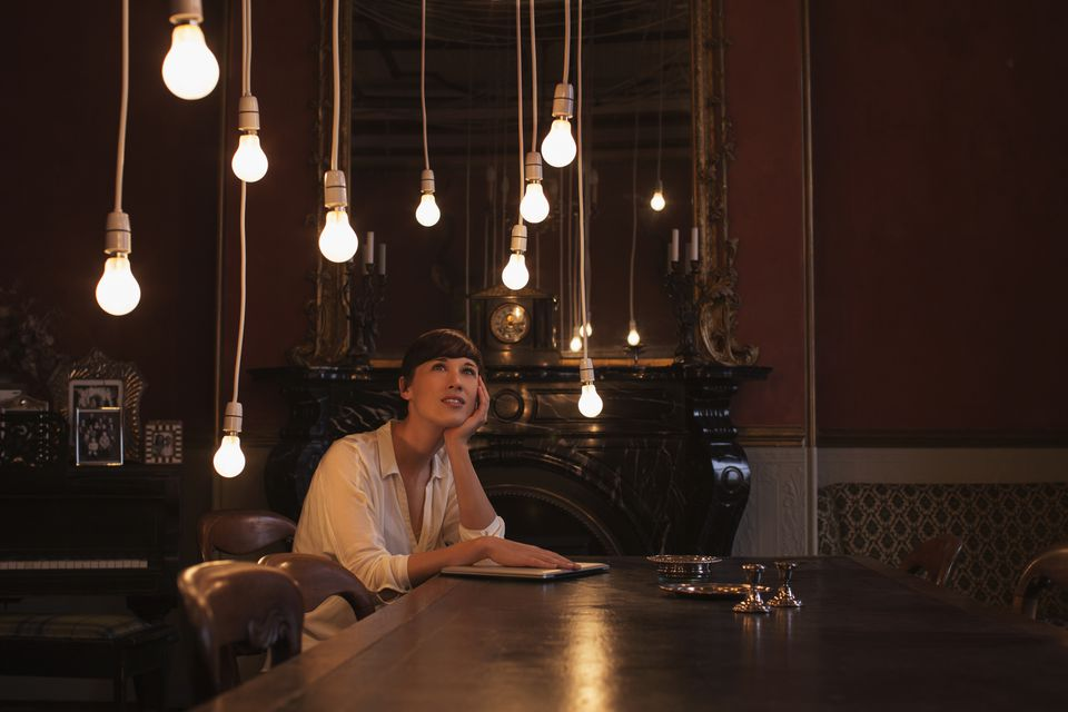 Woman sitting at a table looking up at lightbulbs hanging from the dining room ceiling