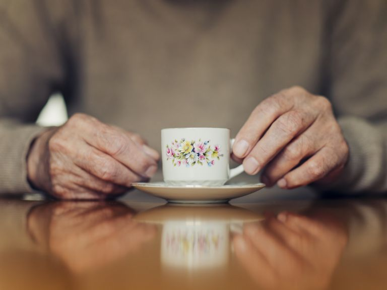 Close-up of older man's hands with a small teacup