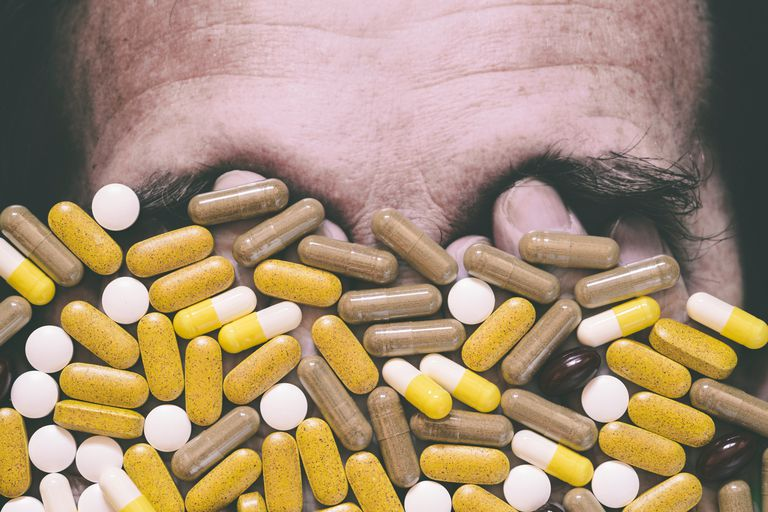 Pills covering photo of man's face