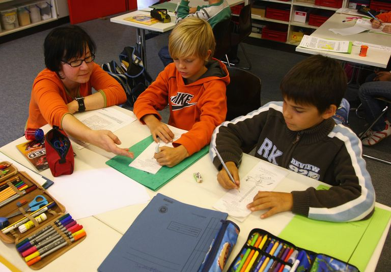 A Teacher Works with Two Boys