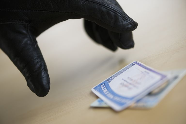 A gloved hand is stealing a social security card and driver's license