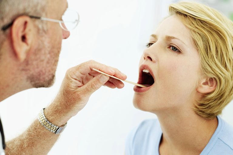 Male doctor examining a young woman's throat with a tongue depressor
