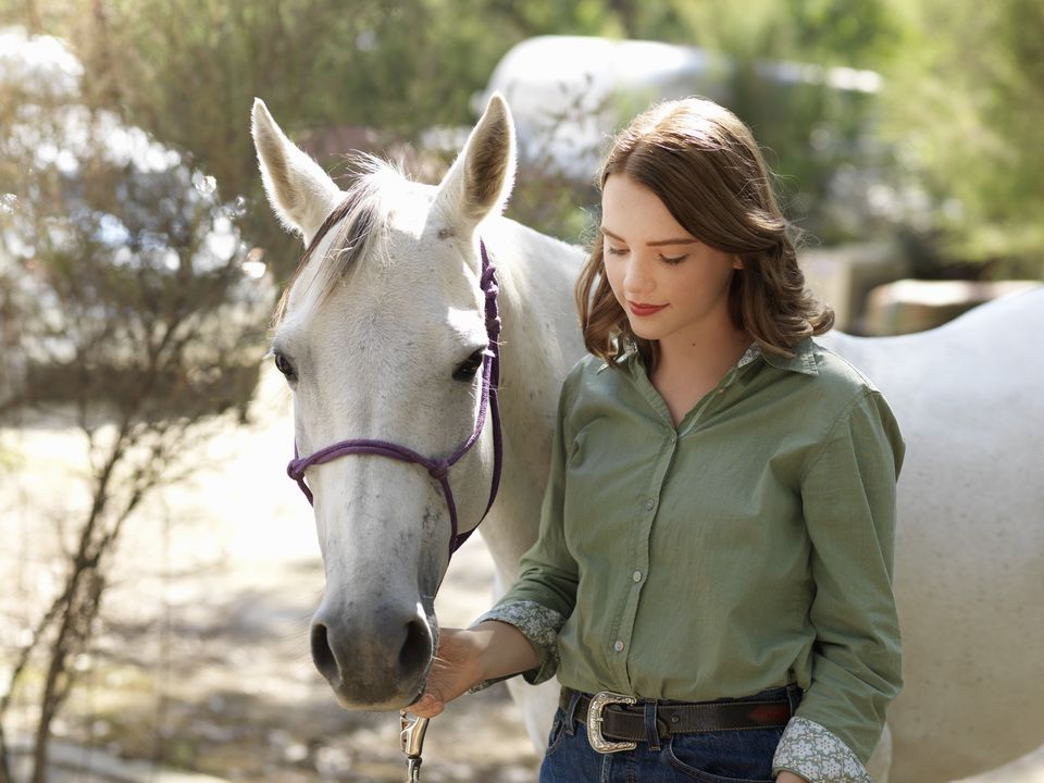 teenage girl with grey horse on farm